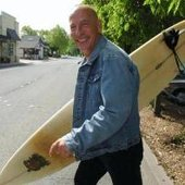 Matthew Larkin Cassell, walking his surfboard across Miller Avenue in Mill Valley,…