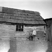 Jilson Setters playing fiddle outside his cabin, 1932.